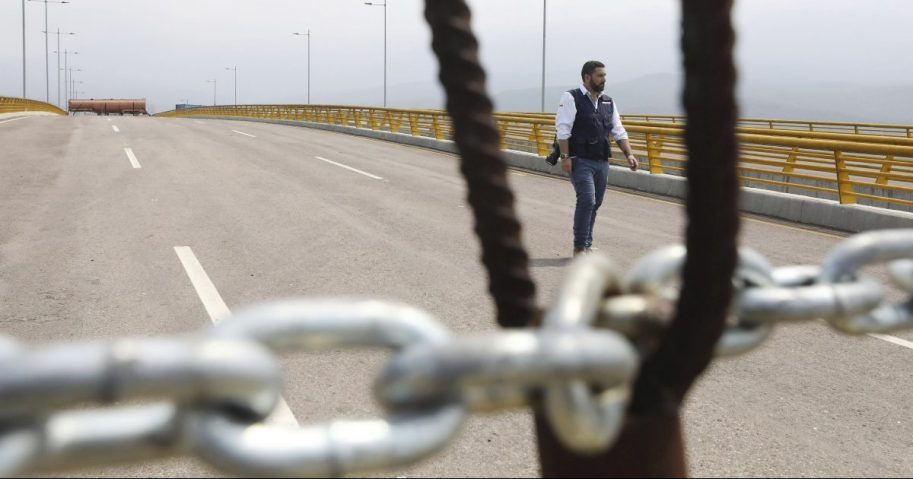 An immigration official walks on the Tienditas International Bridge after Venezuelan authorities used a fuel tanker, cargo trailers and makeshift fencing in an attempt to block humanitarian aid entering from Colombia as seen from the outskirts of Cucuta, Colombia.
