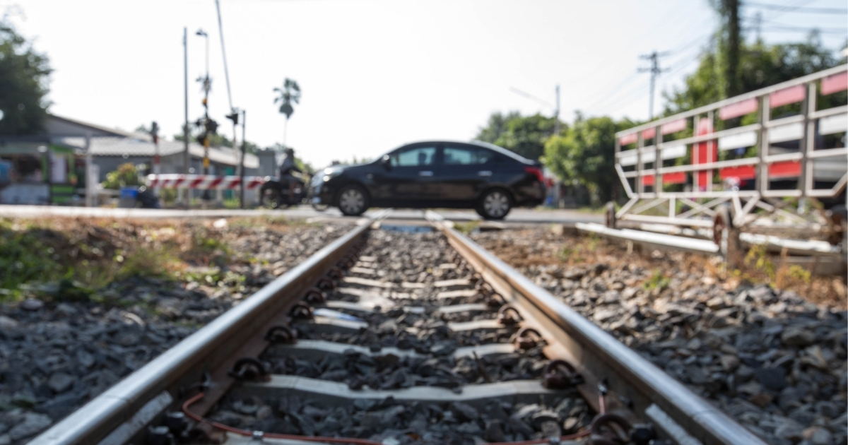 Car in the middle of train tracks.