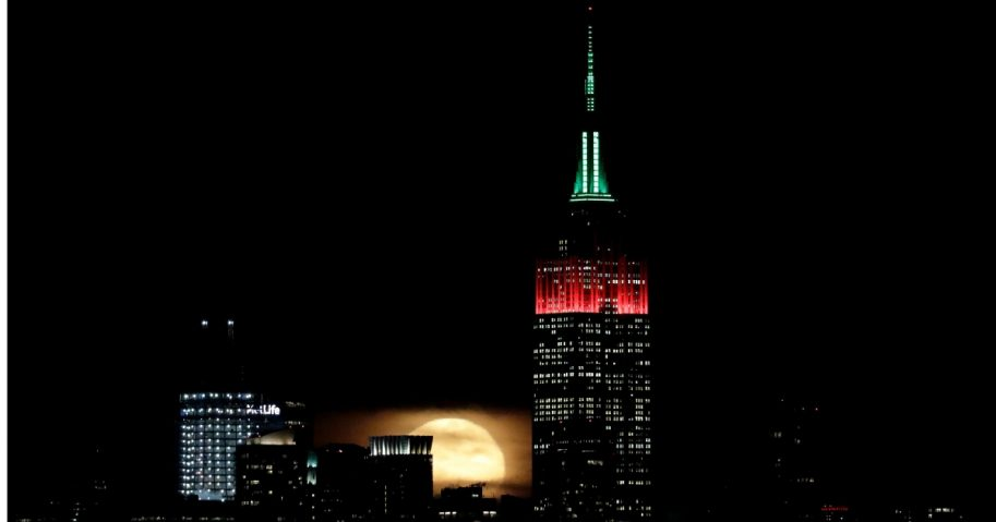 A full moon rises behind New York City near the Empire State Building.