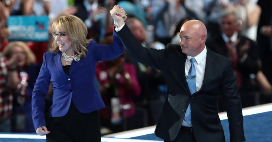 Former Congresswoman Gabby Giffords and her husband, retired NASA Astronaut and Navy Captain Mark Kelly, hold hands as they walk off stage after delivering remarks on the third day of the Democratic National Convention at the Wells Fargo Center, July 27, 2016.
