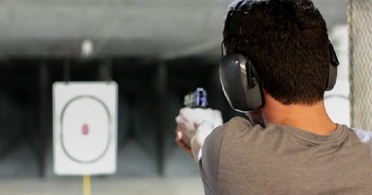 A man firing a handgun at a gun range.