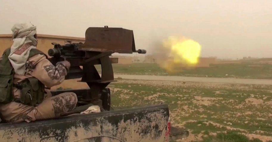 This frame grab from video posted online Jan. 18 by supporters of the Islamic State group purports to show a gun-mounted ISIS vehicle firing at members of the U.S.-backed Syrian Democratic Forces in the eastern Syrian province of Deir el-Zour, Syria.