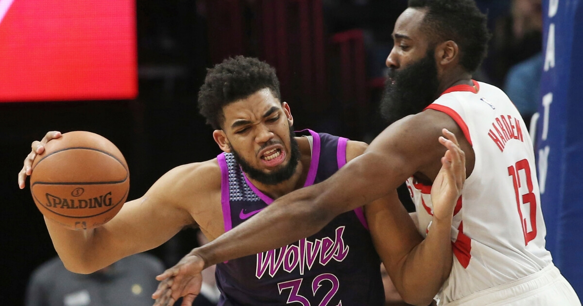 The Minnesota Timberwolves' Karl-Anthony Towns, left, keeps the ball away from the Houston Rockets' James Harden during a Feb. 13 game in Minneapolis.