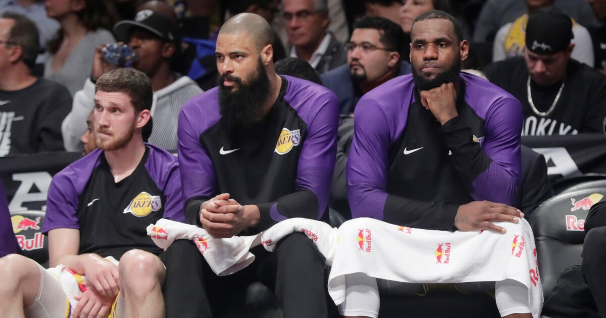 The Los Angeles Lakers' LeBron James, right, and Tyson Chandler, center, watch their team play against the Brooklyn Nets on Dec. 18, 2018, in New York.