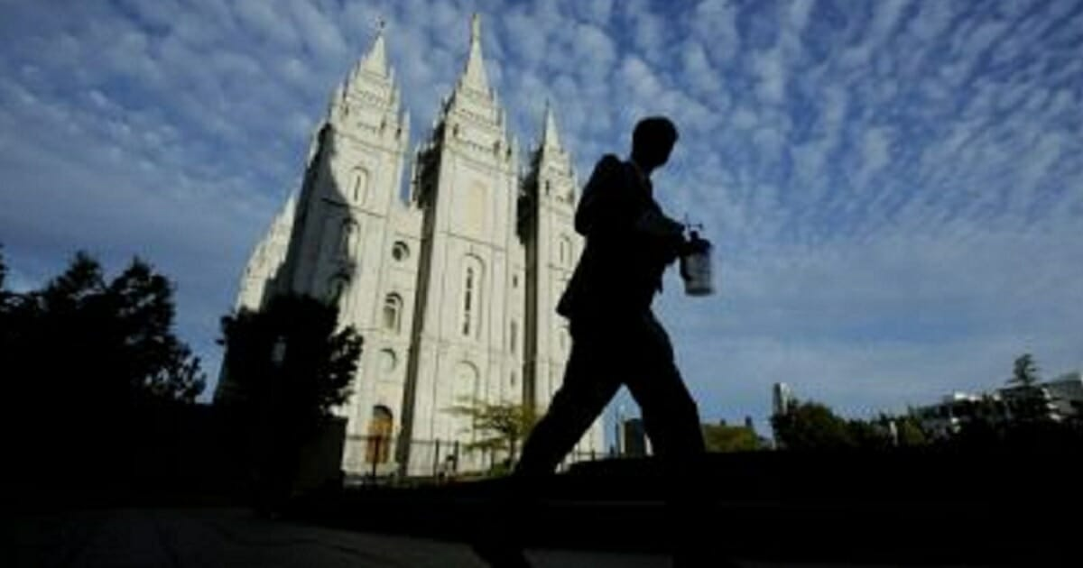 A man walks past the Salt Lake Temple, a temple of The Church of Jesus Christ of Latter-day Saints at Temple Square in Salt Lake City, Utah