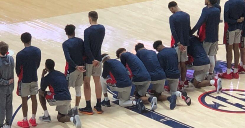 Members of the Ole Miss basketball team kneel in protest during the national anthem.