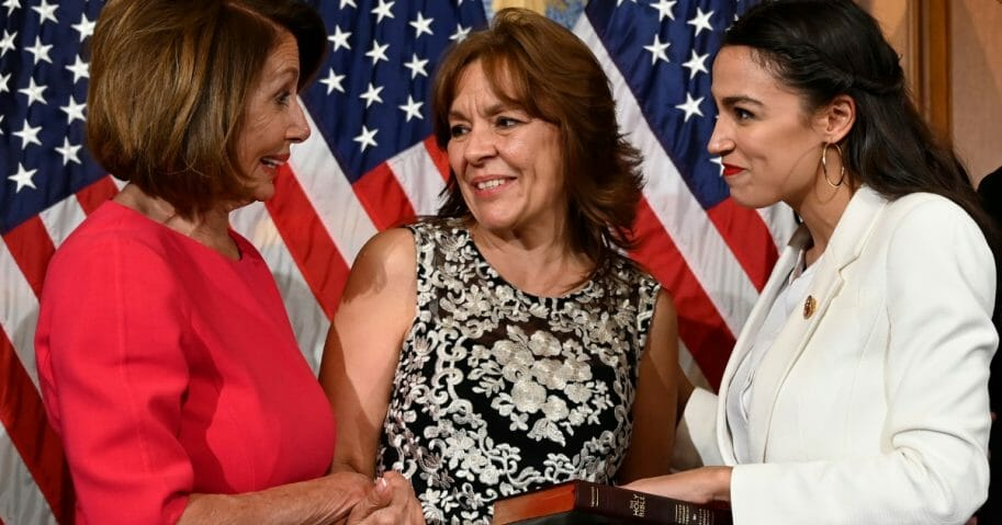 House Speaker Nancy Pelosi, left, talks with Rep. Alexandria Ocasio-Cortez, right, and her mother Blanca Ocasio-Cortez, center, during a ceremonial swearing-in on Capitol Hill in Washington on Jan. 3.