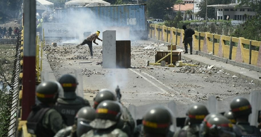 Demonstrators clash with Venezuelan military forces Sunday at the Venezuelan-Colombian border, where Venezuela's military is blocking international aid from entering the country.
