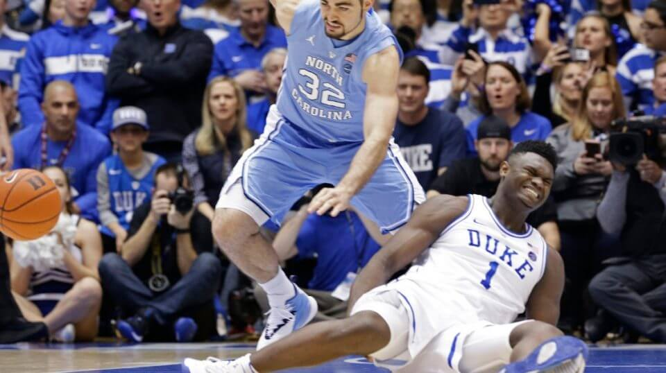 Duke's Zion Williamson falls to the floor with an injury while chasing the ball with North Carolina's Luke Maye during the first half Wednesday in Durham.