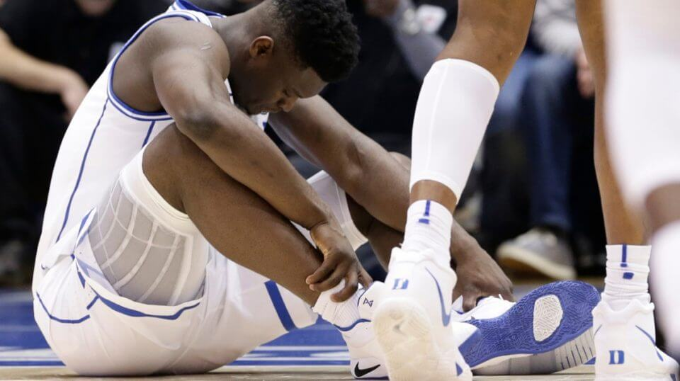 Duke's Zion Williamson sits on the floor looking at his busted Nike shoe during the Blue Devils' game against North Carolina on Wednesday.