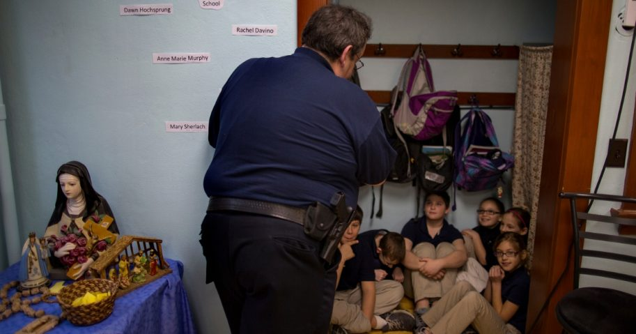 New Washington, Ohio, Chief of Police Scott Robertson talks with fourth grade students as they huddle in closet a during a lockdown drill at the St. Bernard School in New Washington, Ohio.