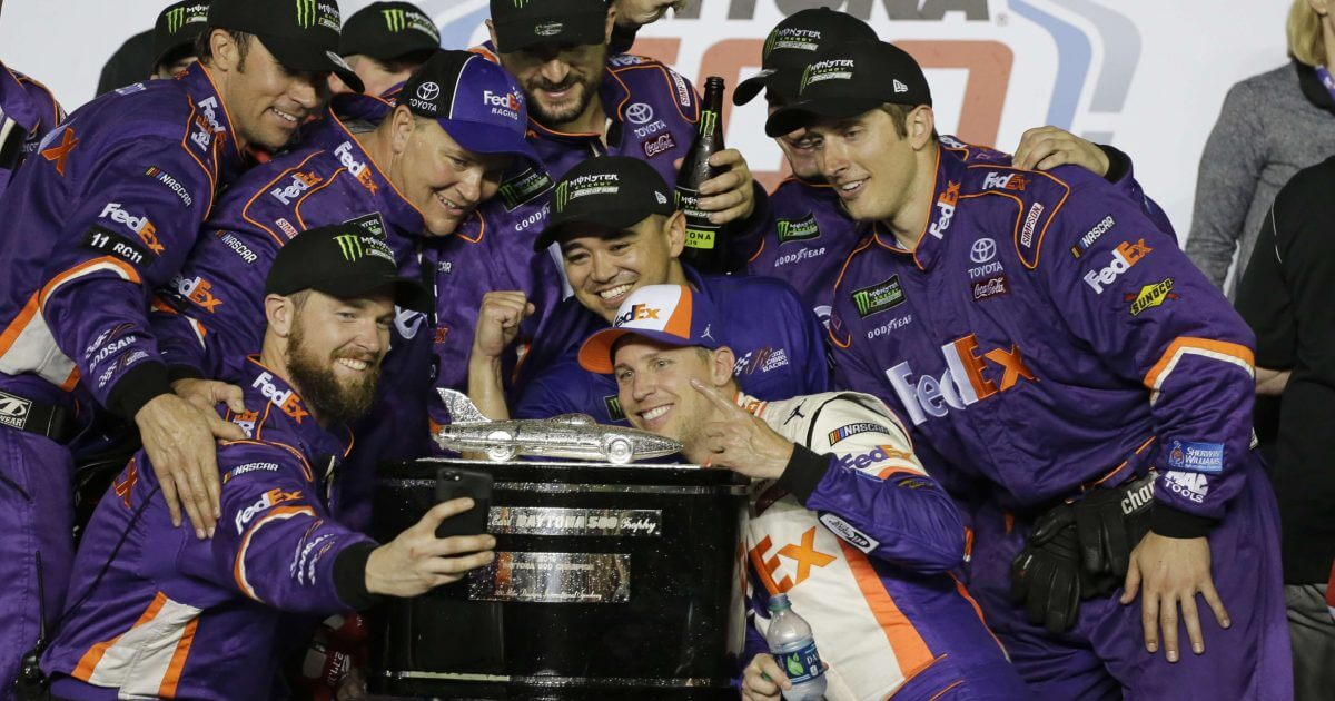 Denny Hamlin, center front, poses for a photo with his crew members after winning the NASCAR Daytona 500 at Daytona International Speedway on Sunday.