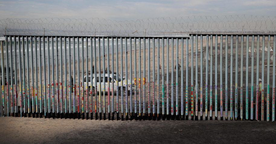U.S. border patrol agents stand watch across the border where the border wall that separates the U.S. and Mexico meets the Pacific Ocean on Jan. 28, 2019, in Tijuana, Mexico.