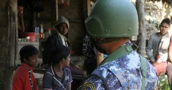 A Myanmar border guard policeman stand near a group of Rohingya Muslims in front of a small store in a village.