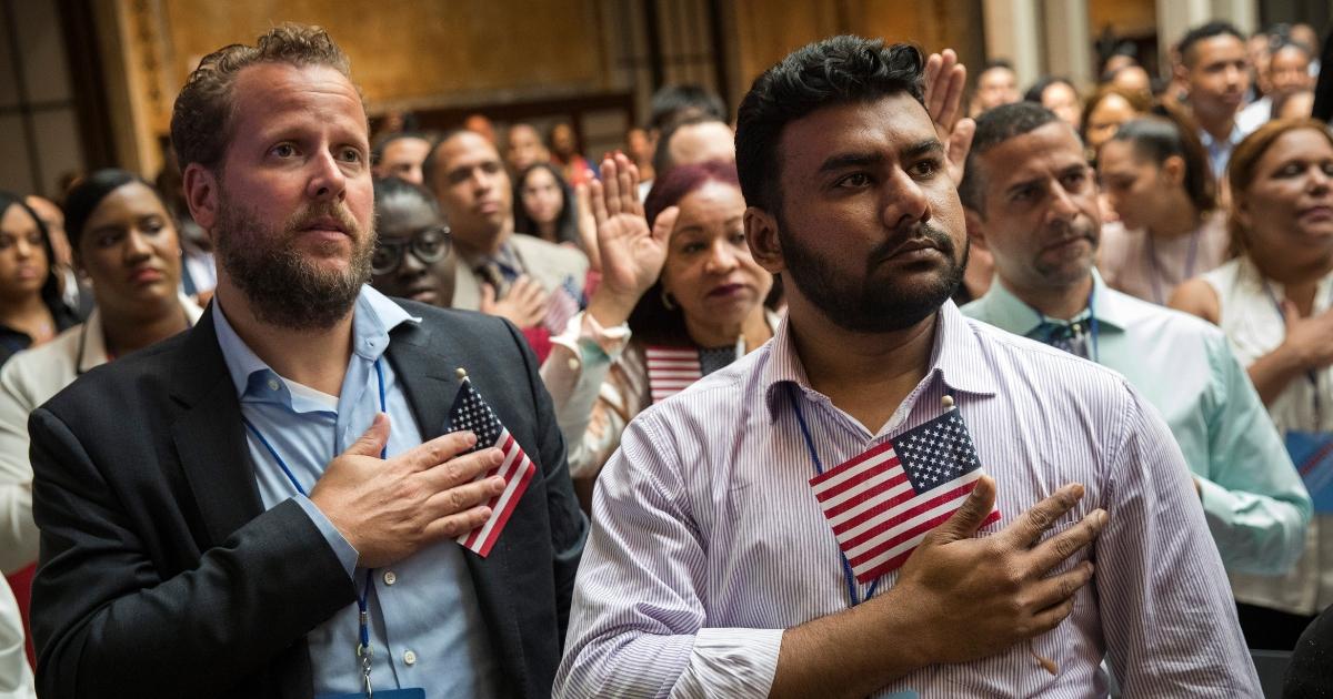 New U.S. citizens recite the Pledge of Allegiance during naturalization ceremony.