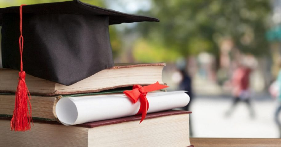 A graduation cap on books with a diploma.