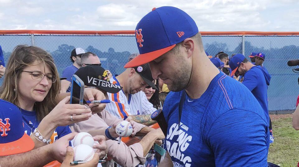 New York Mets prospect Tim Tebow signs autographs at spring training baseball practice on Saturday in Port St. Lucie, Florida.