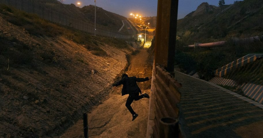 A Honduran youth jumps from the U.S. border fence in Tijuana, Mexico.