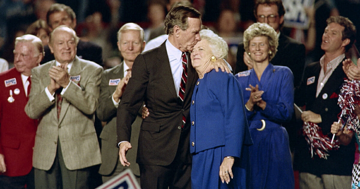US President George Bush kisses his wife Barbara at the end of a rally held at the Astro Arena on November 2, 1992 on the eve of the 1992 presidential election.