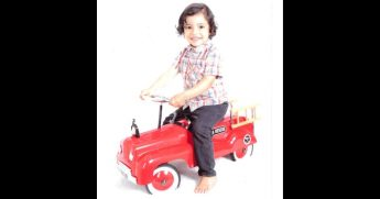 Little boy on a toy firetruck