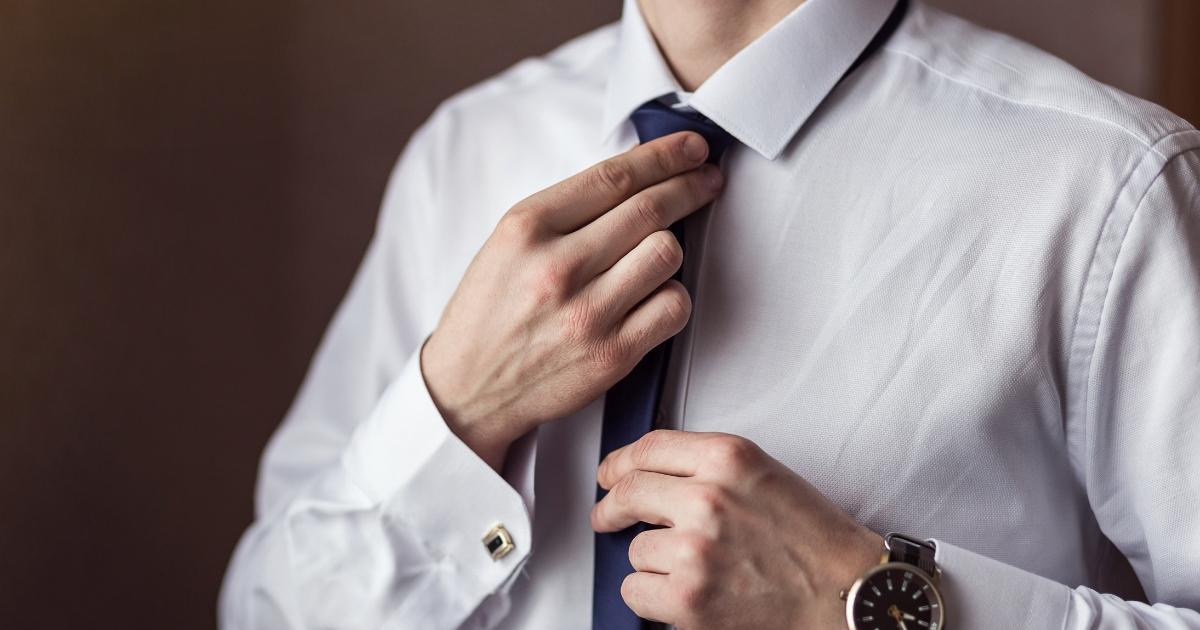 Man in shirt adjusting his tie.