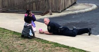 Police officer plays with dolls with young girls.