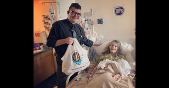 General manager delivers cake to woman in hospital.