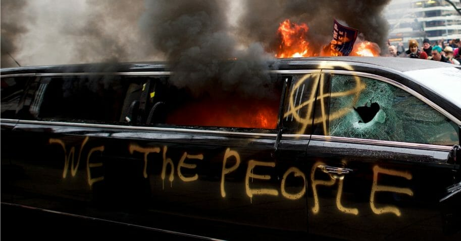 A limousine is set aflame with the graffiti of 'We the People' spray painted on the side after the inauguration of Donald Trump.
