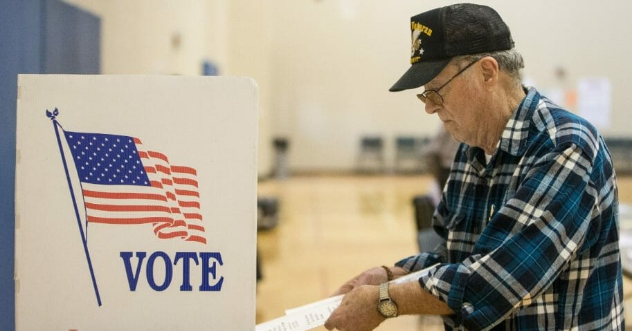 A voter puts in his ballot for the Michigan presidential primary at a polling station in Warren, Michigan.