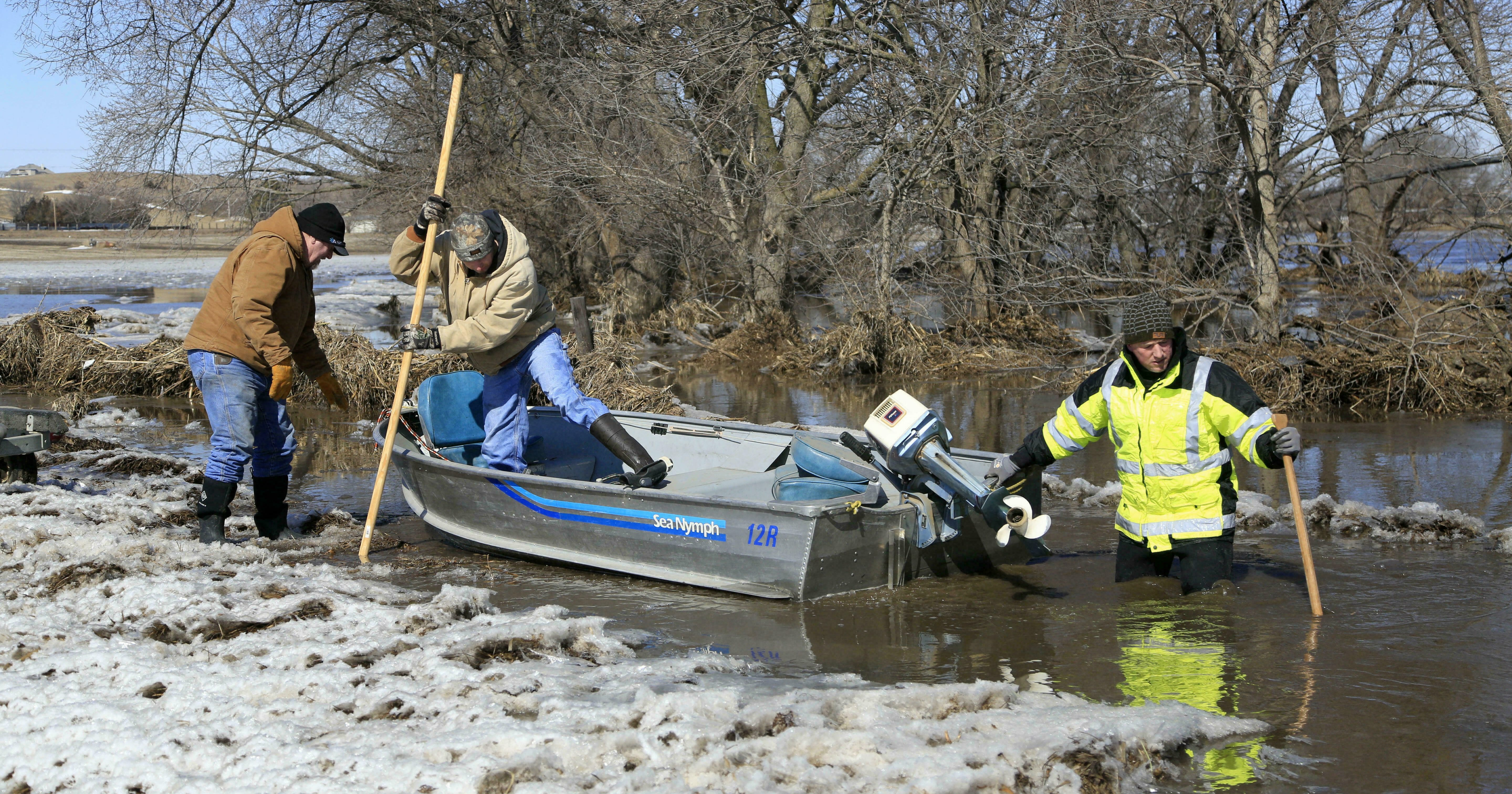 Tom Wilke, left, his son Chad, center, and Nick Kenny launch a boat into the swollen waters of the North Fork of the Elkhorn River, to check on Witke's flooded property, in Norfolk, Nebraska on March 15, 2019.