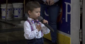Little boy singing at a hockey game.
