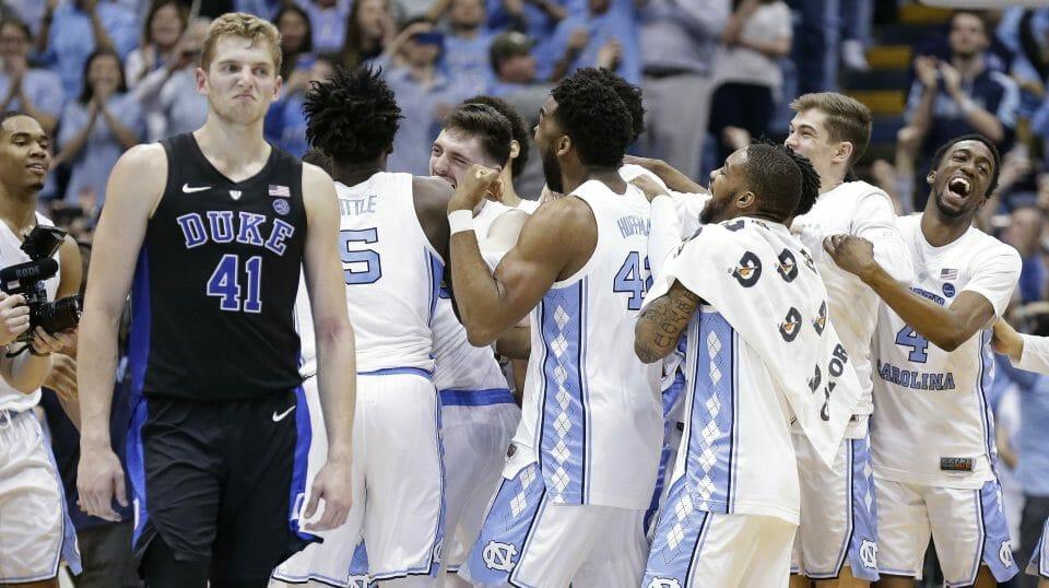 North Carolina players celebrate while Duke's Jack White walks away following an NCAA college basketball game in Chapel Hill, N.C., Saturday, Mar. 9, 2019.