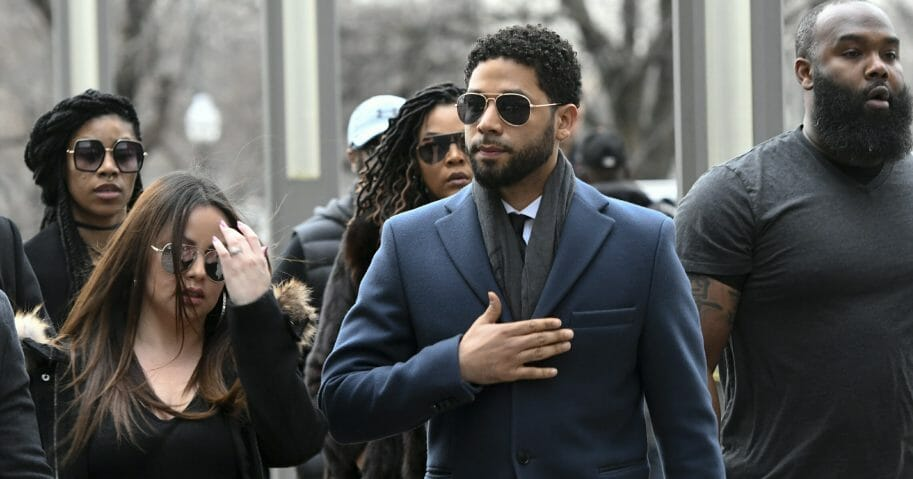 """Empire"" actor Jussie Smollett, center, arrives at the Leighton Criminal Court Building in Chicago for a hearing March 14, 2019."