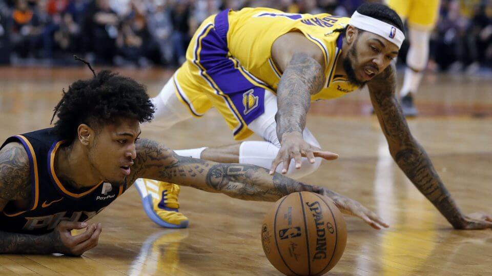 Phoenix Suns forward Kelly Oubre Jr., left, dives for a loose ball in front of Los Angeles Lakers forward Brandon Ingram during the first half of an NBA basketball game Saturday, Mar. 2, 2019, in Phoenix.