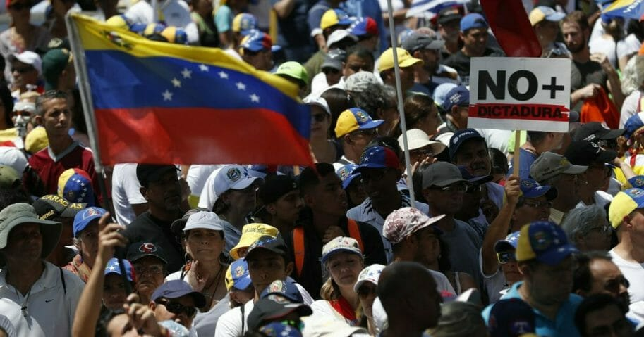 "Anti-government protesters rally to demand the resignation of Venezuelan President Nicolas Maduro, as one holds a sign that reads in Spanish ""No more dictatorship"" in Caracas."