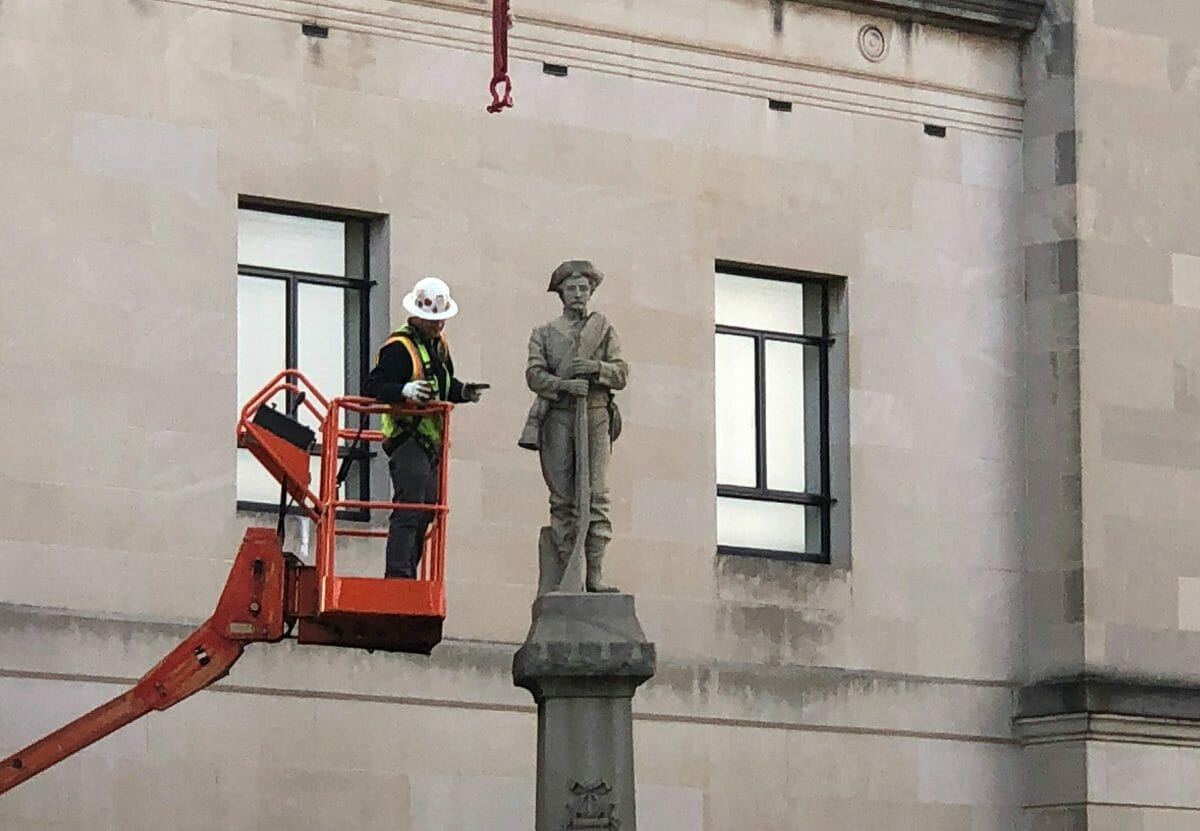A workman prepares a Confederate statue for removal, Tuesday, March 12, 2019, in Winston-Salem, North Carolina.