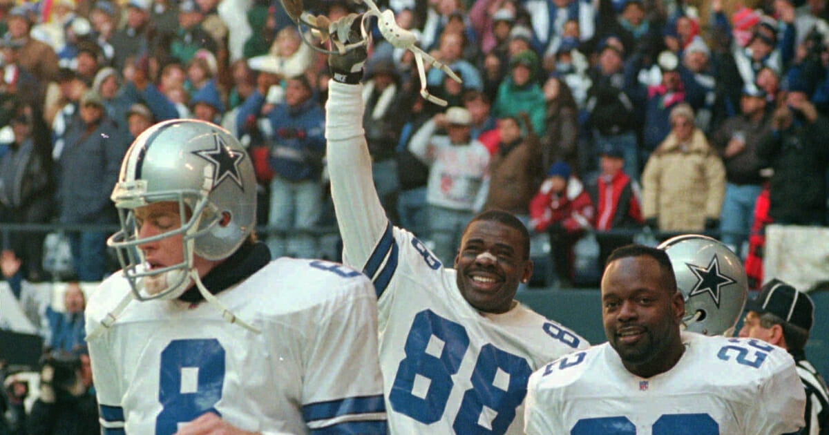 The Dallas Cowboys' Michael Irvin, center, celebrates as he walks off the field with Troy Aikman, left, and Emmitt Smith after catching a fourth-quarter touchdown pass against the Philadelphia Eagles on Jan. 7, 1996.