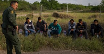 A Border Patrol agent guards a group of illegal immigrants.