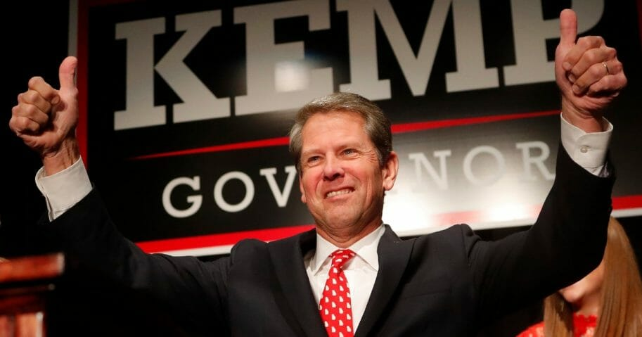 Georgia Gov. Brian Kemp signals to supporters Nov. 7, 2018, in Athens, Ga.