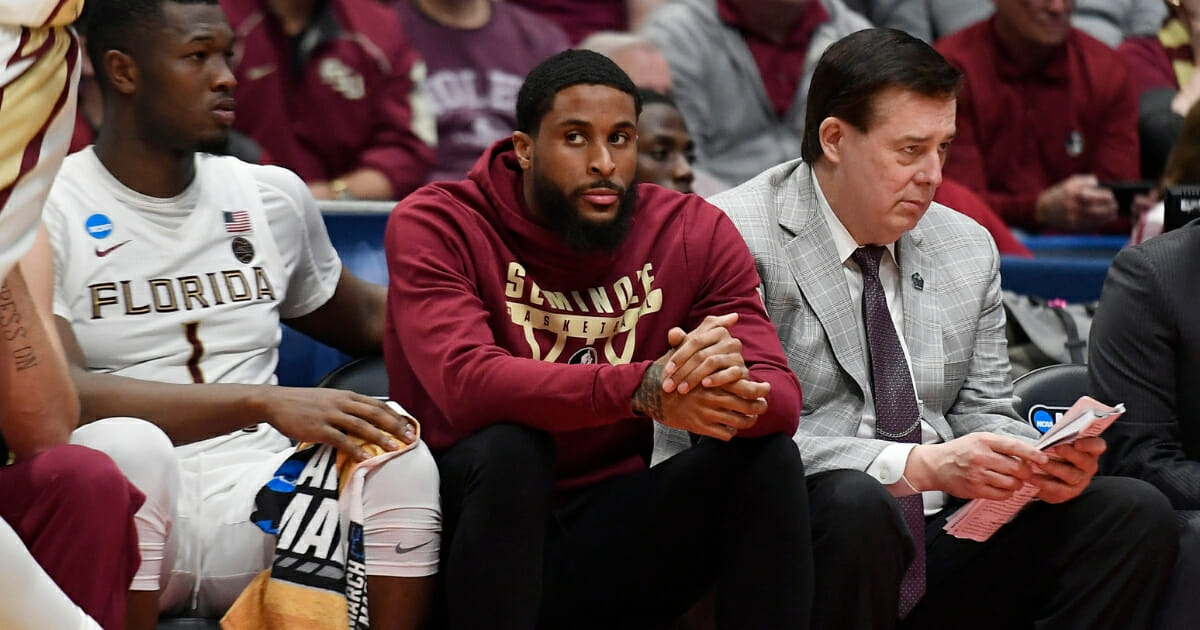 Florida State's Phil Cofer sits on the bench with a boot on his right foot during Seminoles' first-round NCAA Tournament game against Vermont on March 21, 2019.