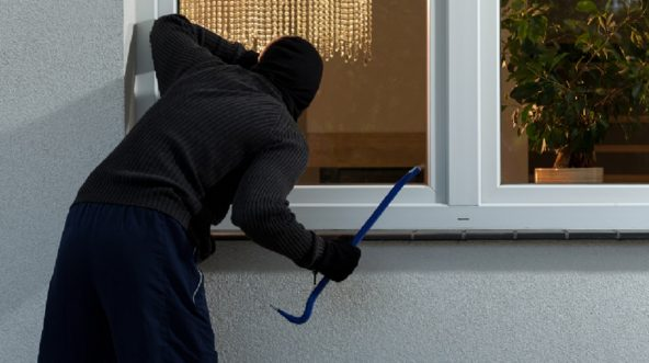 Stock image of man with crowbard near home's window.