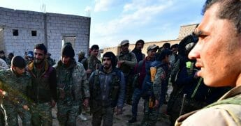 Fighters from Syrian Democratic Forces (SDF) celebrate as they return from the frontline in the Islamic State group's last remaining position in the village of Baghouz on March 19, 2019.