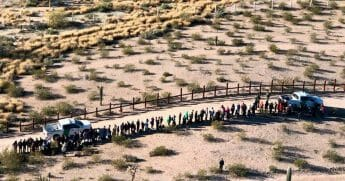 Illegal immigrants line up after they were apprehended along the U.S.-Mexico border near Lukeville, Arizona, Feb. 7, 2019.