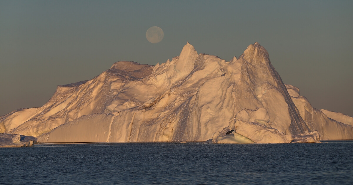 A full moon is seen over an iceberg that broke off from the Jakobshavn Glacier on July 23, 2013, in Ilulissat, Greenland.
