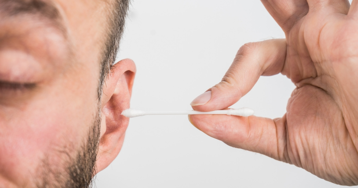 Man cleaning his ear with a cotton swab.