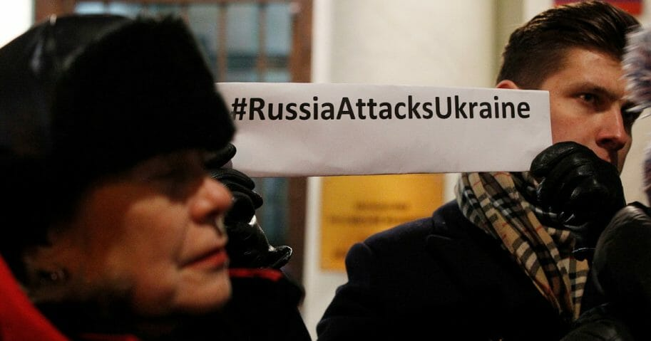 Protesters hold a banner in front of the Russian Embassy in Warsaw, Poland, on Monday, Nov. 26, 2018.