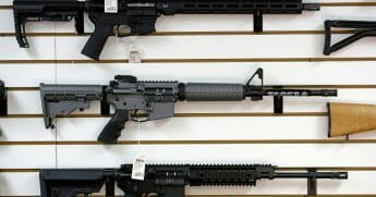 Rifles for sale at a gun store include a Ruger AR-15 semi-automatic rifle, center.