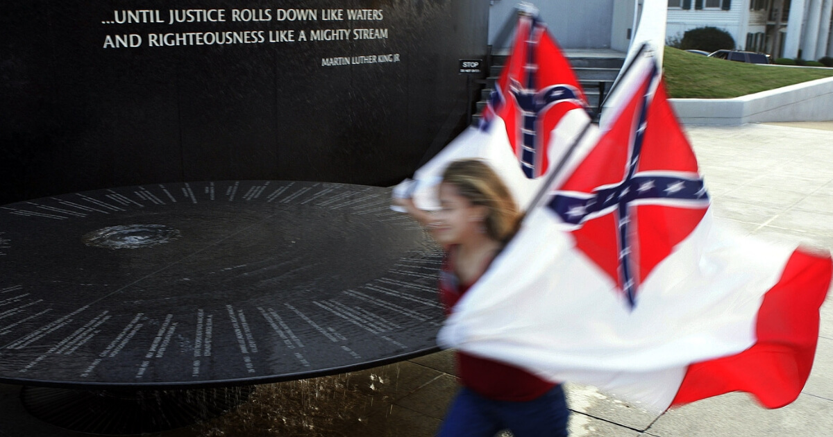 A woman carries Confederate battle flags past the Civil Rights memorial outside the Southern Poverty Law Center in Montgomery, Ala.