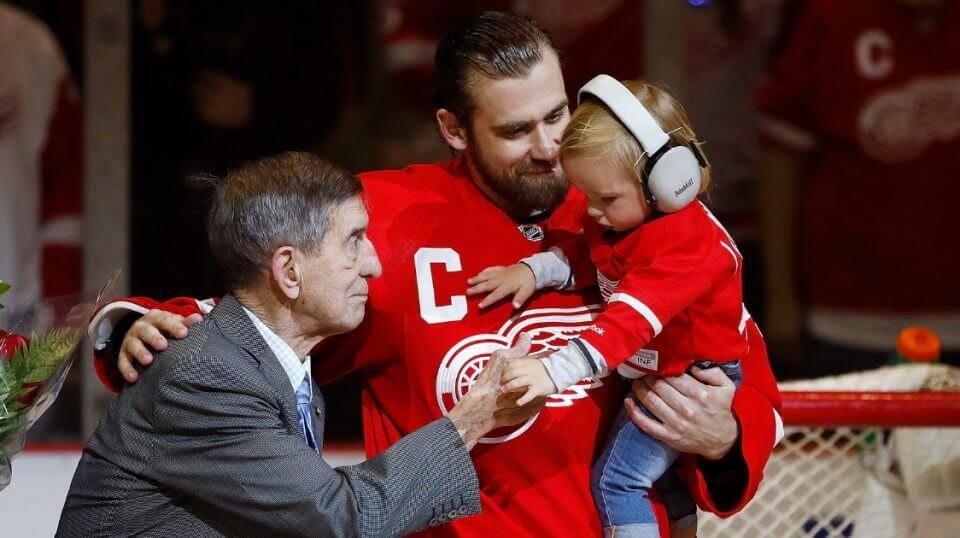 Henrik Zetterberg, center, of the Detroit Red Wings, his son Love and Red Wings legend Ted Lindsay during presentation to honor his 1000th NHL game prior to a game against the New Jersey Devils at Joe Louis Arena on April 9, 2017 in Detroit.