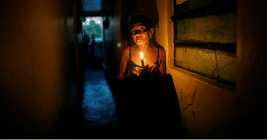A Venezuelan woman uses a candle to navigate in through her home in the Santa Cruz of the East neighborhood of Caracas during the country's huge power outage on March 14.